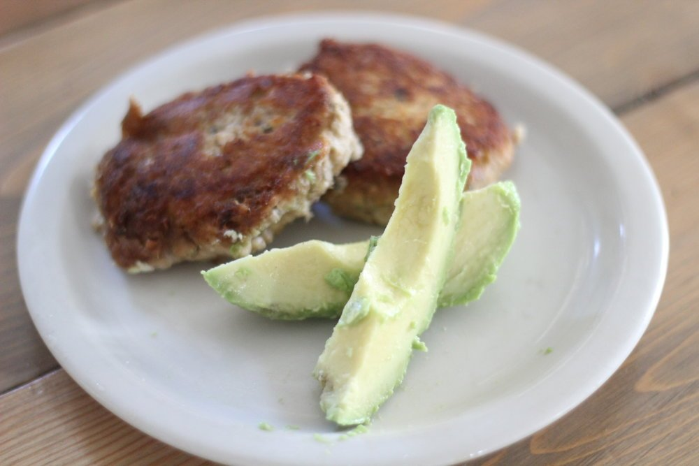 two crispy salmon burgers on a white plate with sliced avocado