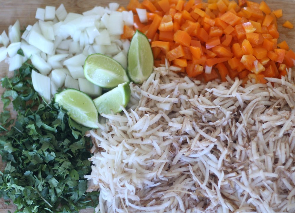 chopped up onions, orange peppers, lime quarter, and shredded potatoes