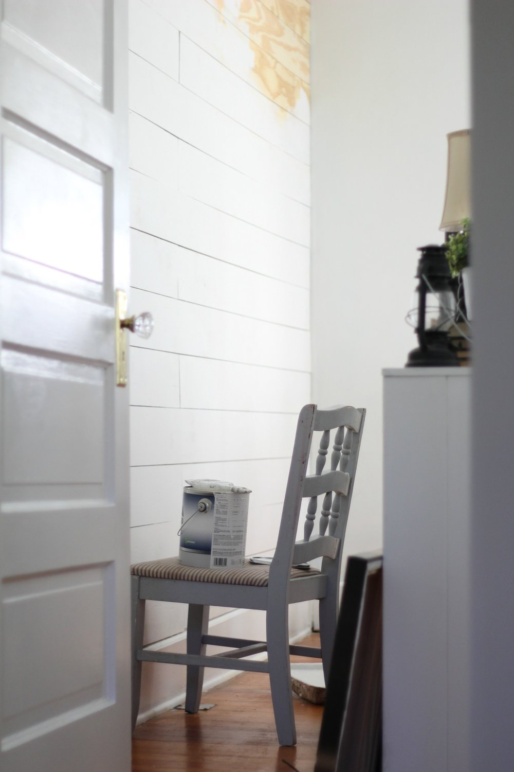paint on a chair that is being painted onto a DIY Shiplap wall.