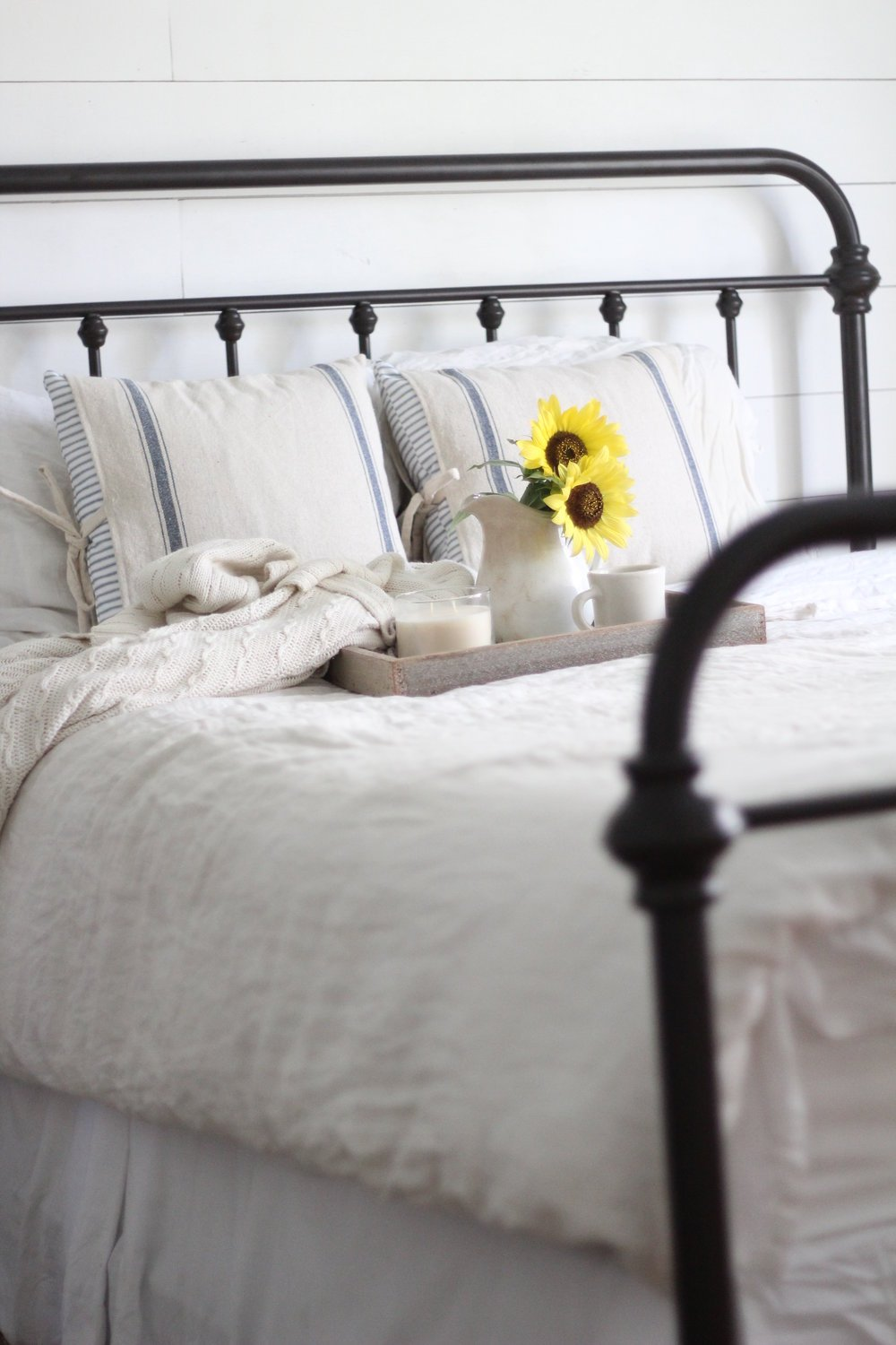 iron bed with linen bedding and a serving tray with a vase of flowers