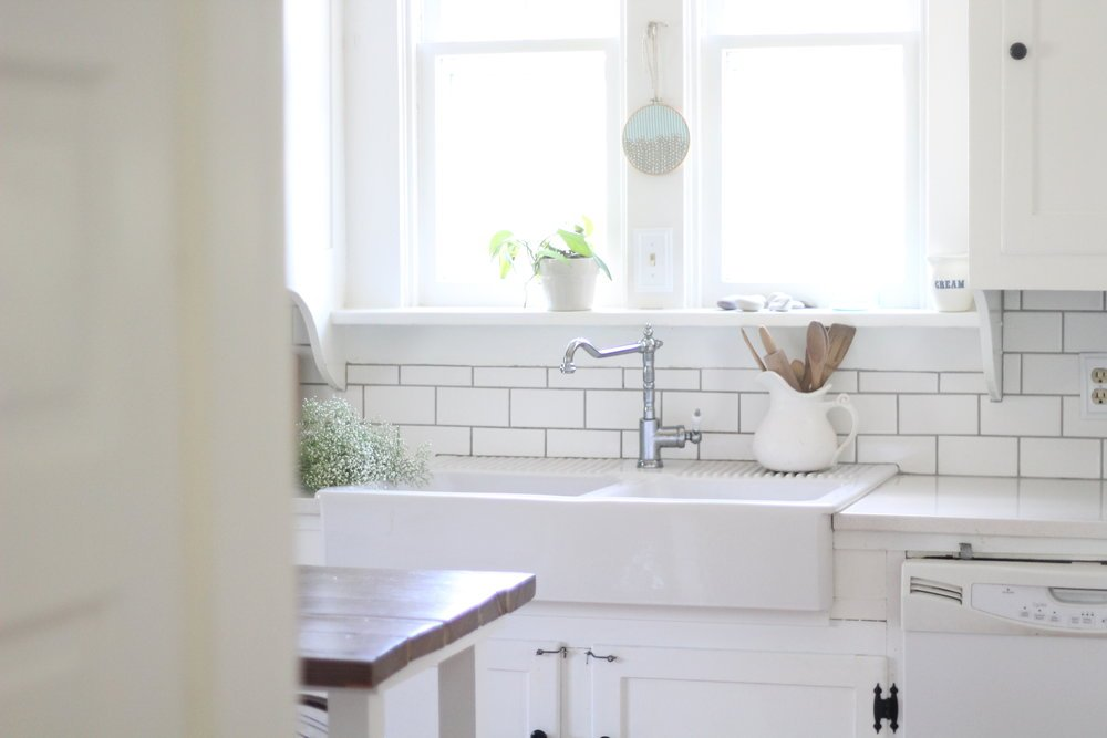 farmhouse kitchen with an ikea farmhouse sink, faucet, and white countertops