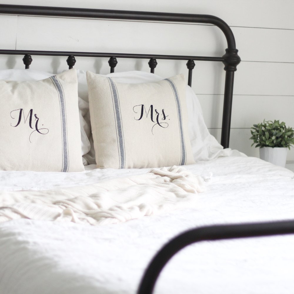 iron bed with linen bedding. a faux ikea plant in a white pot to the right