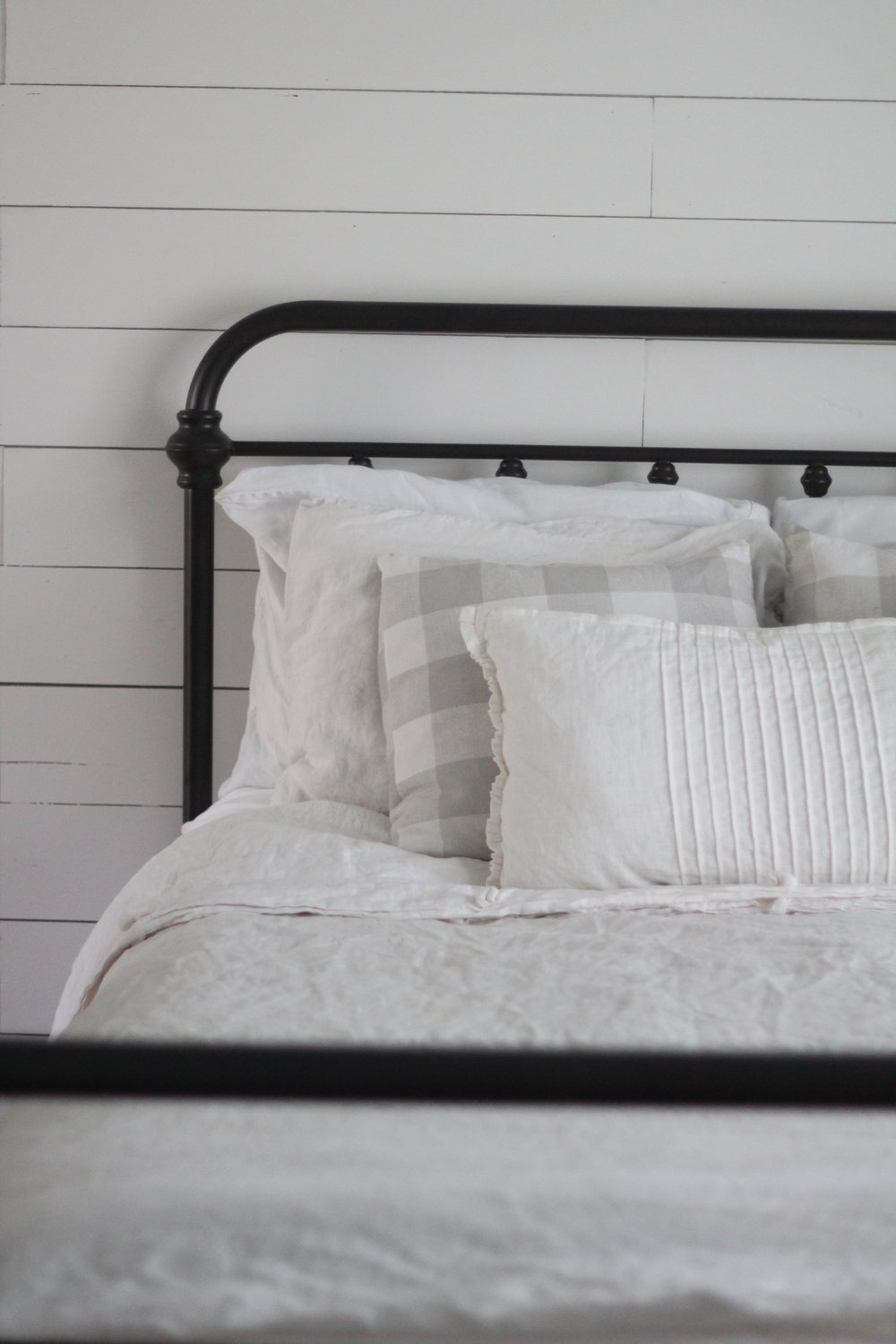 iron bed with linen pillows and duvet covers