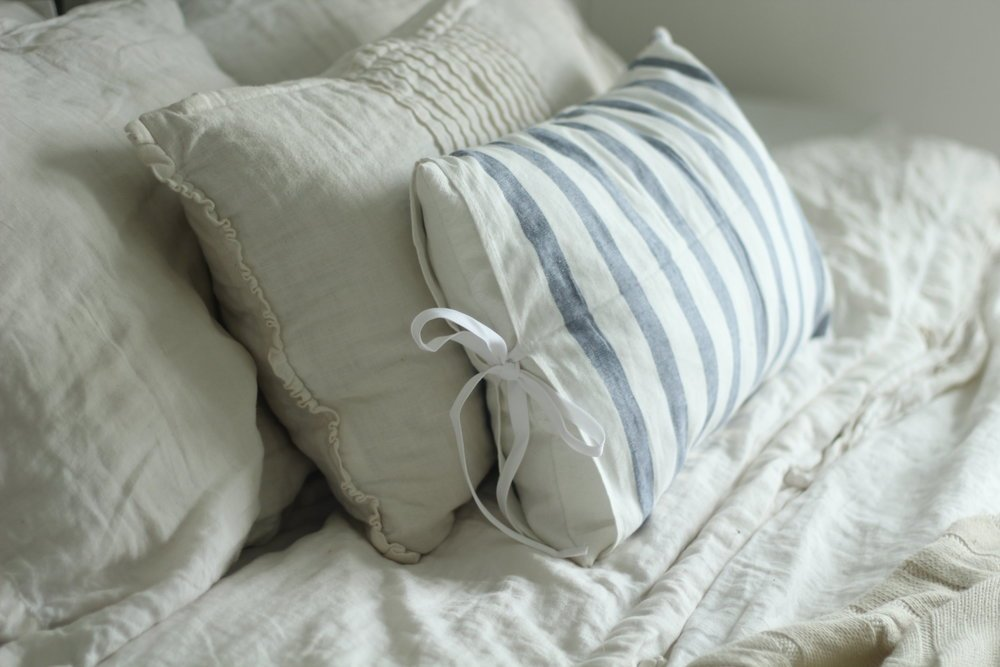 linen duvet and pillows on a bed. A blue and white stripped ikea towel pillow in front