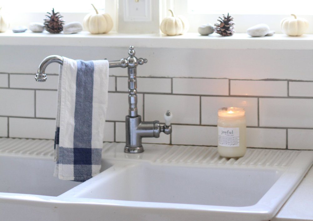 ikea farmhouse sink with a antique inspired faucet and a ikea tea towel hanging off the faucet. A candle is to the right.