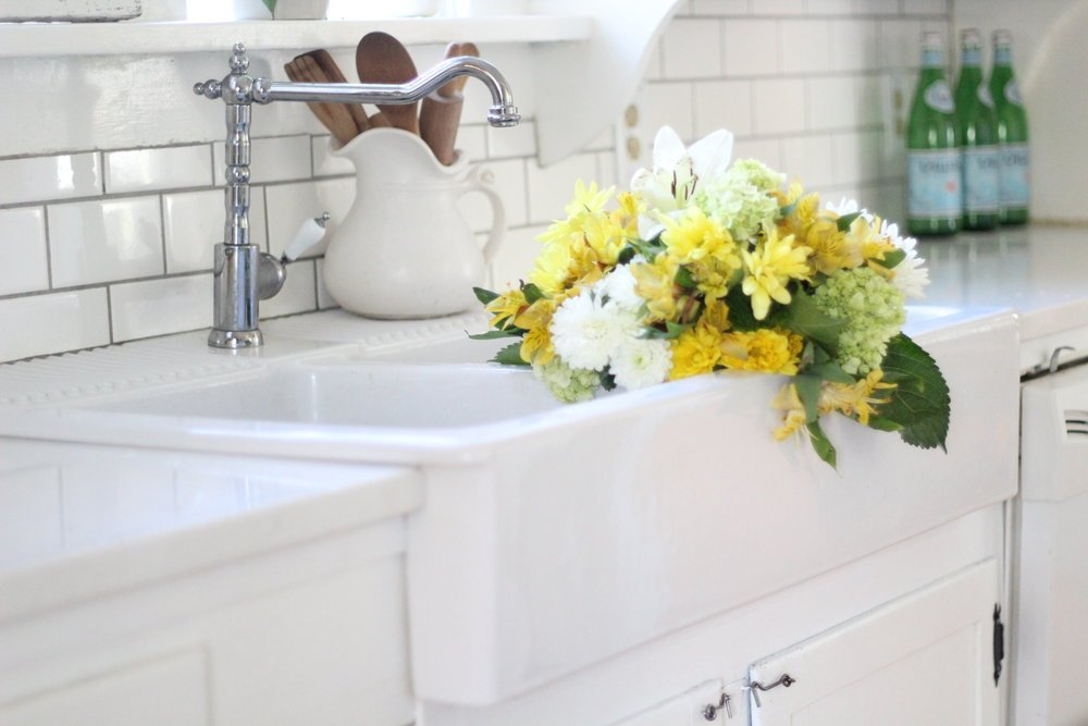yellow and white flowers in a ikea farmhouse sink.