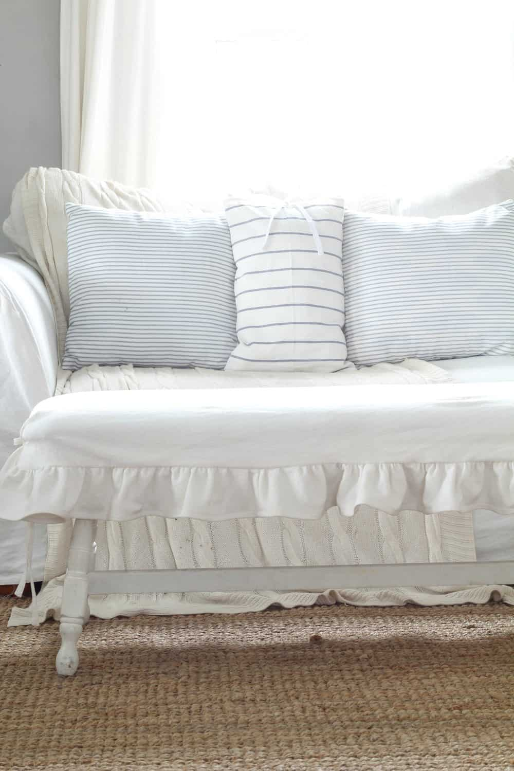 white bench with ruffle slipcover with a white couch with blue pillows in the background