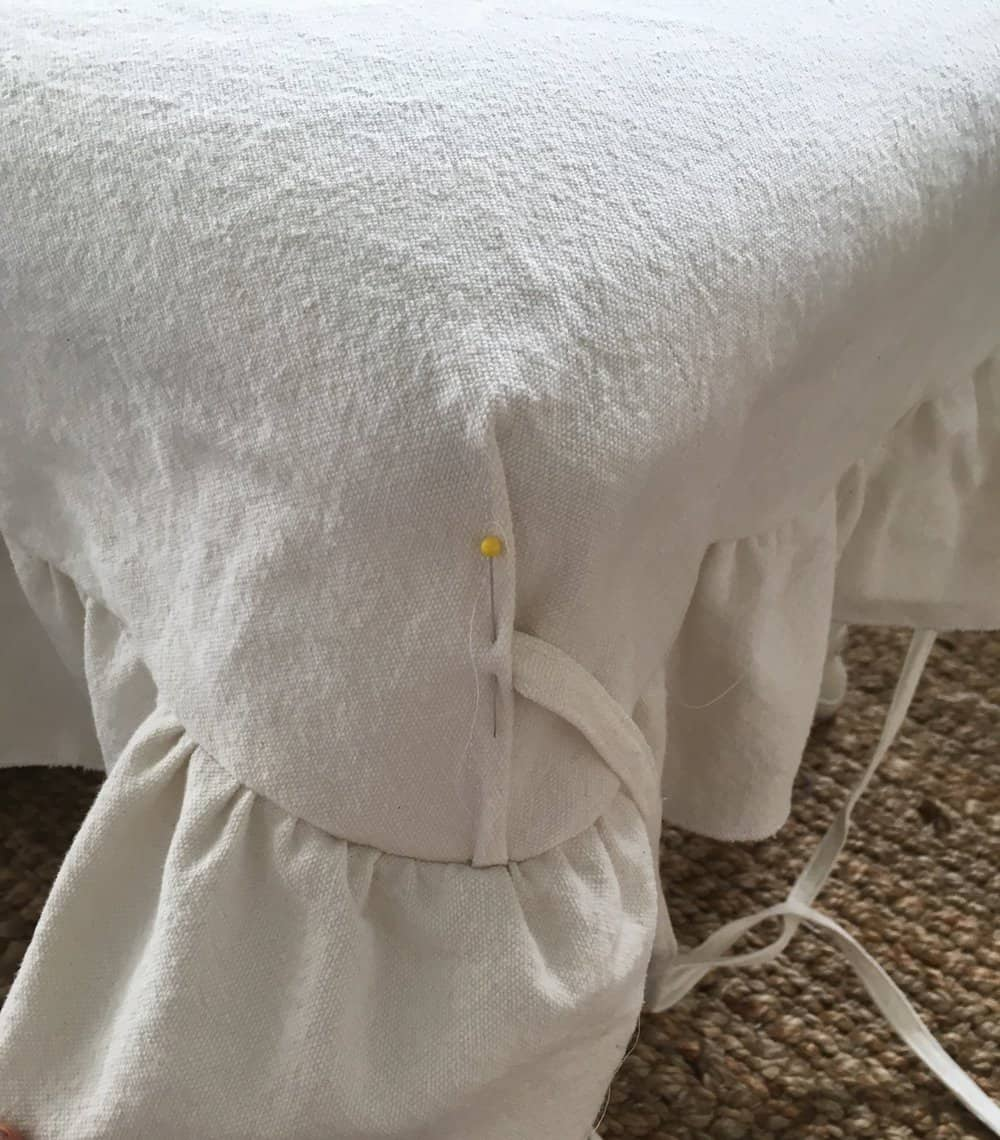 pinning ties to the corners of a drop cloth bench cover