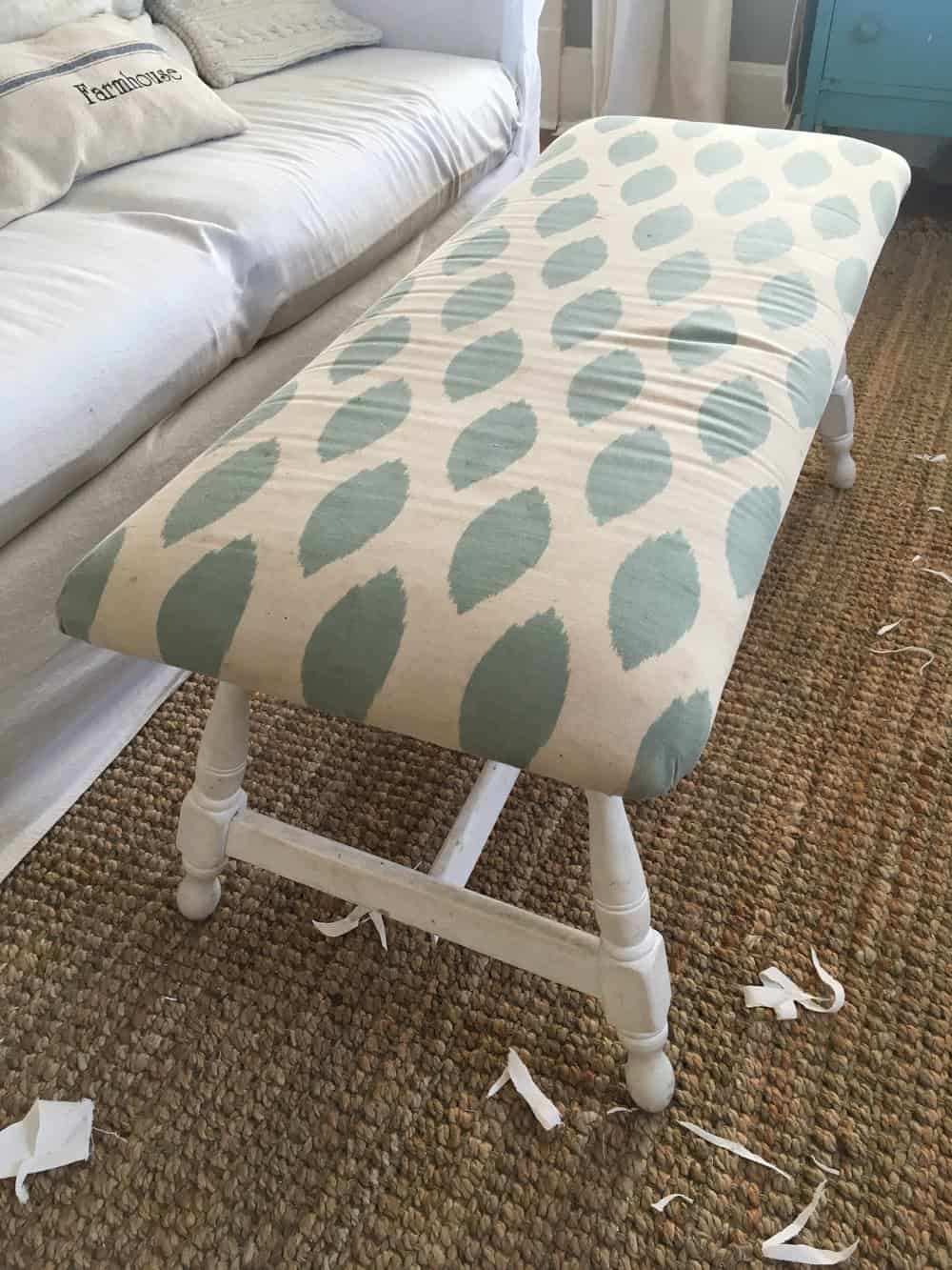 a white bench with a creamy and teal cushion top
