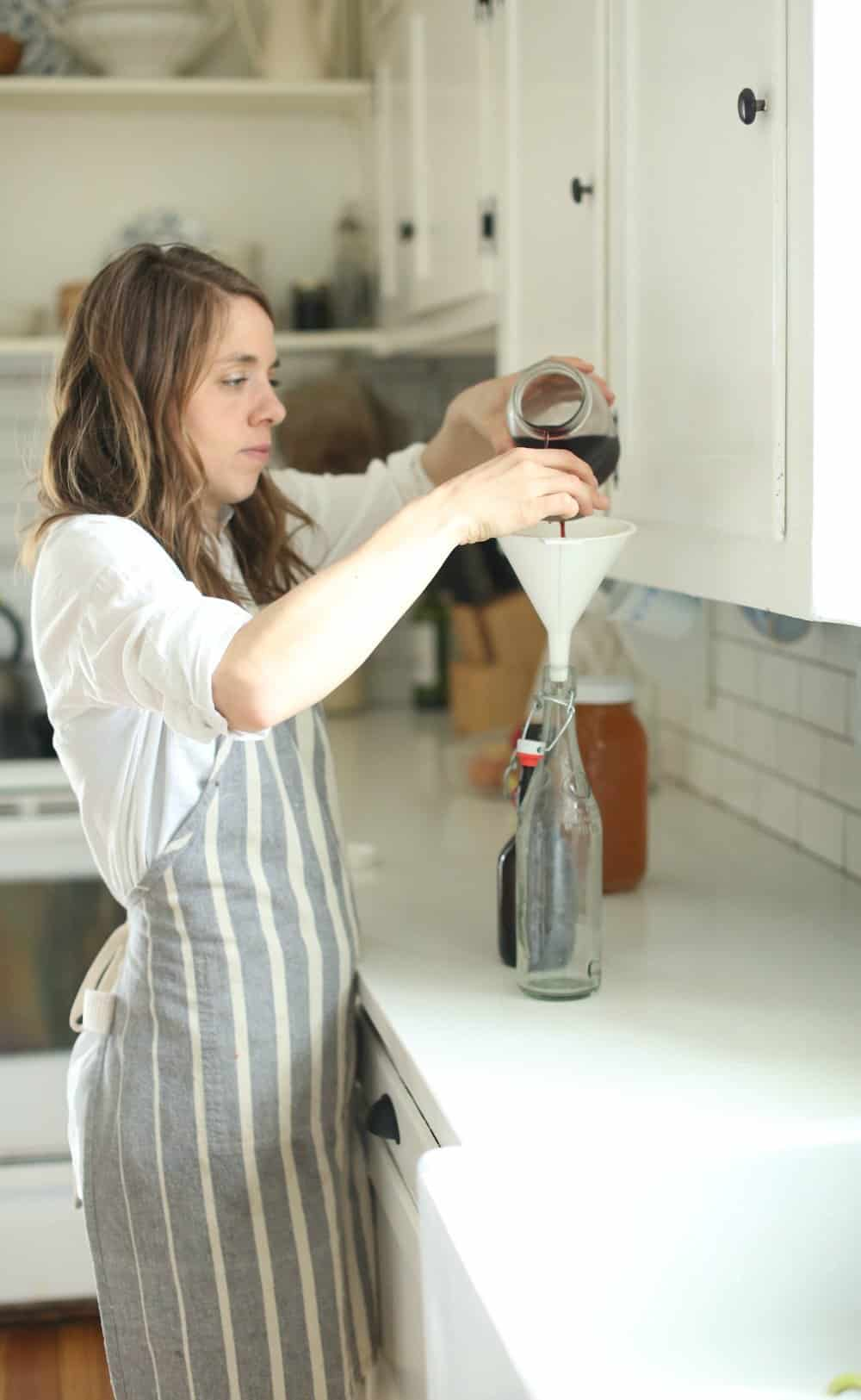 women pouring grape juice into a flip-top glass bottle to make water kefir soda
