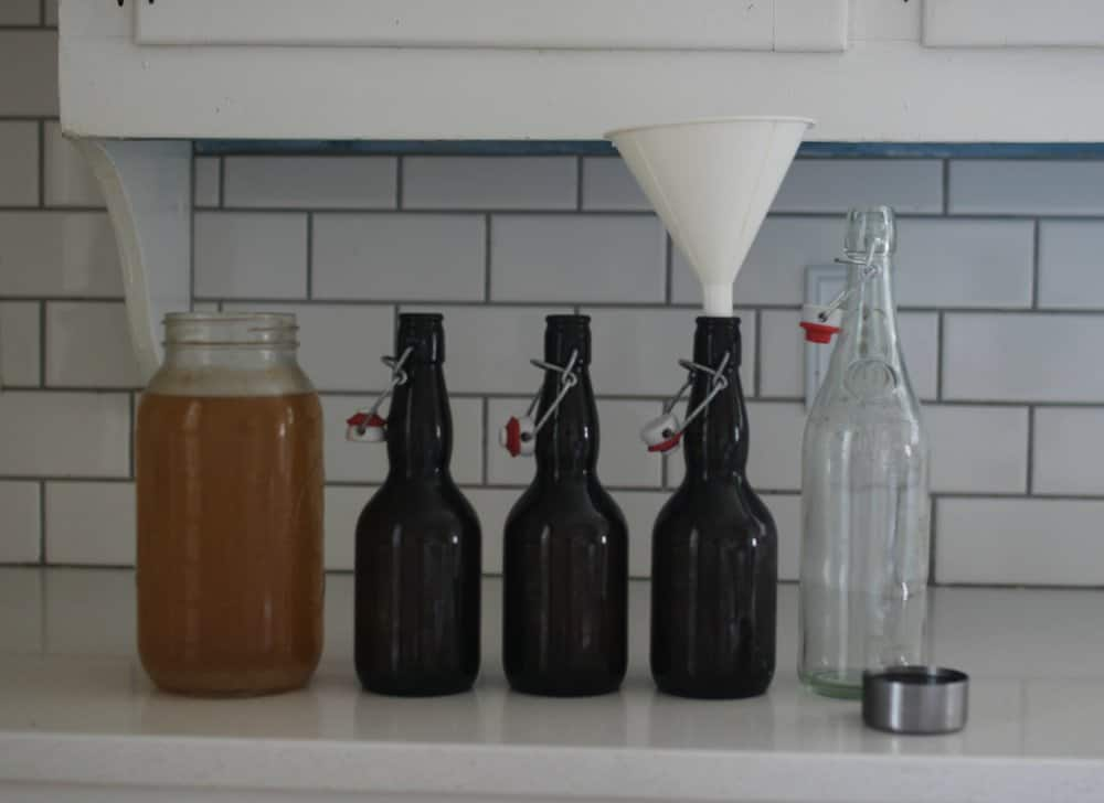 half gallon mason jar filled with water kefir with four empty bottles ready for bottling to the right