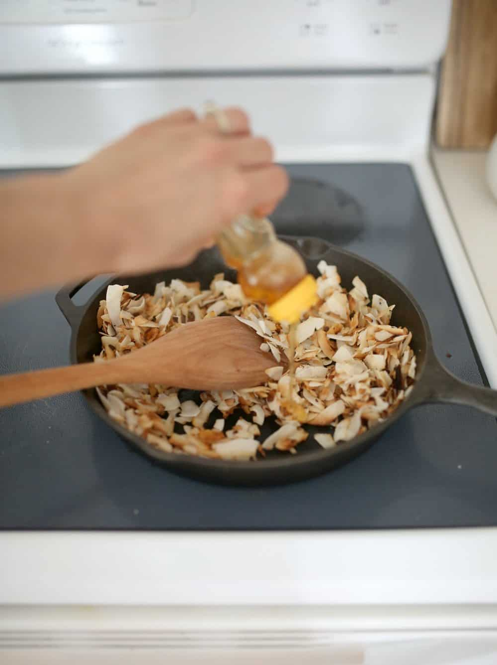 adding honey to toasted coconut chips in a cast iron skillet