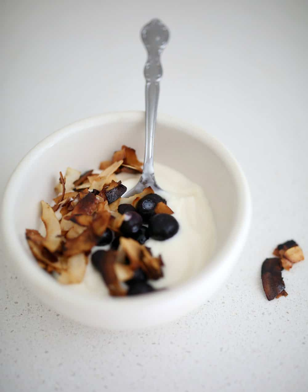 yogurt topped with toasted coconut chips and blueberries in a white bowl with a metal spoon