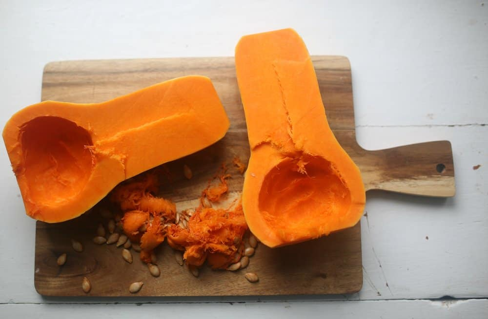 butternut squash sliced in half with seeds taken out on a cutting board