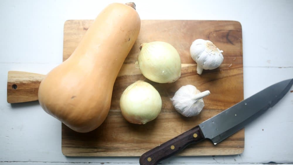 butternut squash, two onions, and two head of garlic on a cutting board with a knife - roasted butternut squash soup