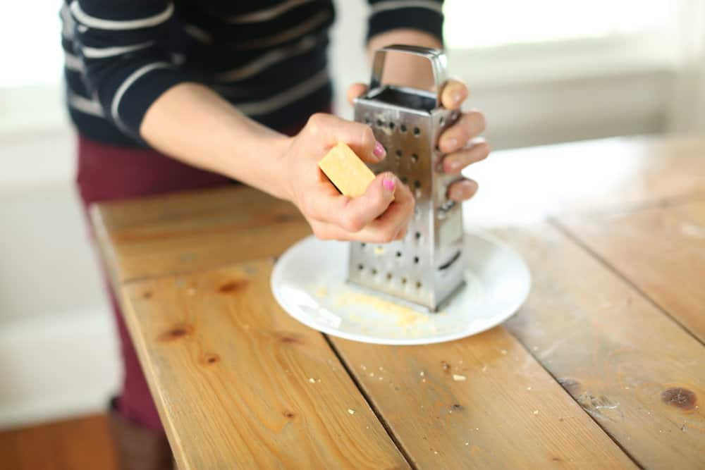 women creating Fels naphtha soap with a cheese grater on a plate to make homemade laundry soap