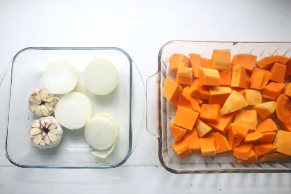 onions, garlic, and chopped butternut squash in glass baking dishes
