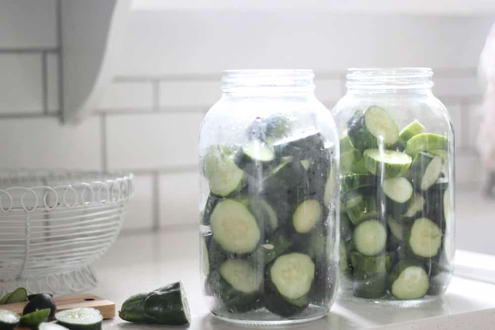 two larger gallon sized mason jars with sliced cucumbers