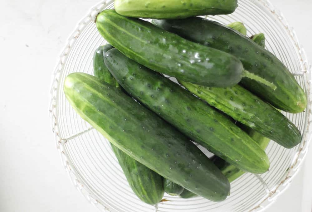 overhead shot of cucumbers in a white white basket.